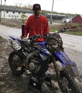 man posing with dirtbike and trophy